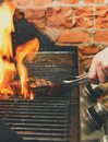 Man cooking meat steaks on professional grill outdoors Royalty Free Stock Photo