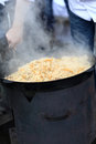 Man cooking pilaf the is in outdoor uzbek restaurant Royalty Free Stock Photo
