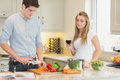 Man cooking with woman drinking red wine women in kitchen Stock Photography