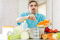Man cooks lunch wit vegetables handsome at kitchen Stock Photography