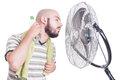 Man cooling his neck with cold water bottle and fan Royalty Free Stock Photo