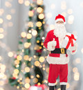 Man in costume of santa claus with gift box christmas holidays and people concept showing thumbs up gesture over tree lights Royalty Free Stock Photos