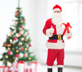 Man in costume of santa claus with gift box holidays and people concept showing thumbs up gesture over living room and christmas Stock Images