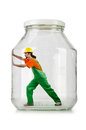 Man in coveralls imprisoned glass jar Stock Photos