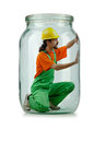 Man in coveralls imprisoned glass jar Royalty Free Stock Photography