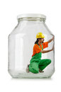 Man in coveralls imprisoned glass jar Royalty Free Stock Images