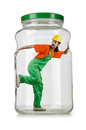 Man in coveralls imprisoned glass jar Stock Photography