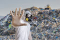 Man in coveralls is showing stop gesture. Garbage pile in landfill in background Royalty Free Stock Photo