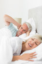 Man covering ears while woman shouting in bed closeup of a men women at home Stock Photo