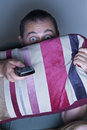 Man covering face with a cushion watching tv close up Royalty Free Stock Images