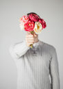 Man covering his face with bouquet of flowers Stock Images