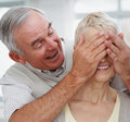 Man covering wife's eyes surprising her Stock Photo