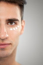 Man with cream portrait of cosmetic on skin around the eyes Stock Images