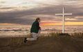 Man at cross beautiful sunset as kneels down to pray god before a Royalty Free Stock Photos