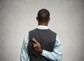 Man crossing fingers behind his back closeup young businessman conceptual image business with crossed isolated black Royalty Free Stock Images