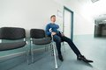Man with crutches sitting on chair Royalty Free Stock Photo