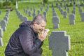 Man crying near the soldier s grave on Stock Photos