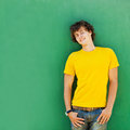 Man with curly hair in a yellow t shirt on green background Stock Photo