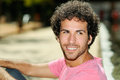 Man with curly hairstyle smiling in urban background Royalty Free Stock Image