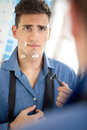 Man cuts himself shaving unhappy young looking his on face after Royalty Free Stock Images