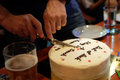Man cutting birthday cake in dimmed light pub, birthday party concept Royalty Free Stock Photo