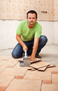 Man cutting ceramic floor tiles looking in the camera Stock Image