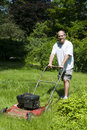 Man cutting grass at suburban house Royalty Free Stock Photo