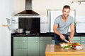 Man cutting vegetables at kitchen counter portrait of handsome smiling Stock Photos