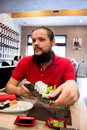 Man with dark hair and long beard holding a plate with tasty sushi in a restaurant Royalty Free Stock Photo