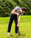Man digging a a hole on the grass Stock Photo