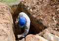 Man digs grave in blue cap at cemetery Royalty Free Stock Photo