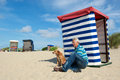 Man with dog at beach borkum sitting the of german wadden island typical striped chair Royalty Free Stock Photo