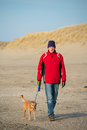 Man with dog at the beach walking dutch in winter Stock Photos