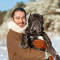 Man and dog friendship forever a in a winter forest with cane corso Royalty Free Stock Photo