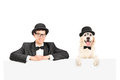 Man and dog with hats posing behind panel Royalty Free Stock Images