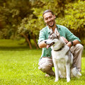 Man and dog in the park husky walk he keeps on leash Royalty Free Stock Image