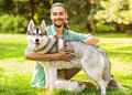 Man and dog in the park husky walk he keeps on leash Royalty Free Stock Photography