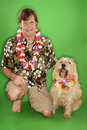 Man with dog wearing leis. Stock Image