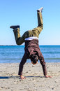 Man doing acrobatic on beach show an cartwheel equilibrium Stock Images