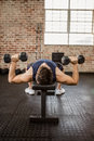 Man doing exercise with dumbbells while lying on bench Royalty Free Stock Photo