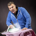 Man doing housework angry and ironing a shirt Stock Images