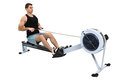 Man doing indoor rowing exercising on machine hands slightly blurred in motion Royalty Free Stock Photos