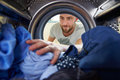 Man Doing Laundry Reaching Inside Washing Machine Royalty Free Stock Photo