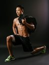 Man doing lunge exercises with sand bag photo of a muscular lunges a Stock Photos