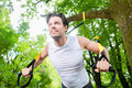 Man doing suspension trainer sling sport exercising with in city park under summer trees for fitness Stock Image
