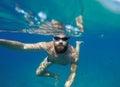Man doing underwater selfie shot with selfie stick in blue sea