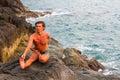 Man doing yoga exercise on the deserted wild stone sea beach sport Royalty Free Stock Photos