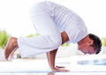 Man doing yoga meditating in a hard position Stock Photo