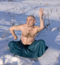 Man doing yoga over snow in winter Royalty Free Stock Photos