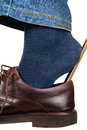 Man dons brown shoes using shoe horn isolated Royalty Free Stock Photo